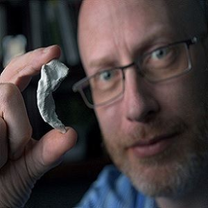 Neurobiologist Craig Stark holding a 3D model of his own hippocampus