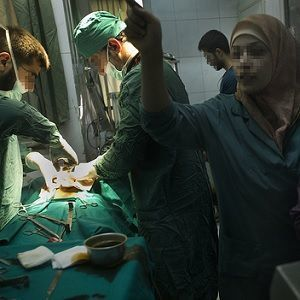 a wounded man being treated in a field hospital in Syria