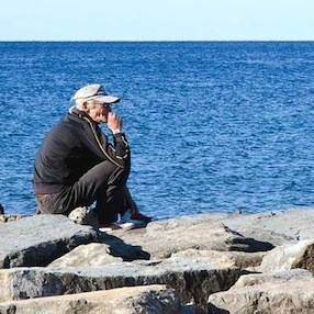 Old man sitting on the breakwater - acciaroli.info