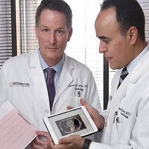 Cardiologists Dr. James de Lemos (left) and Dr. Amit Khera (right) review a printout from an EKG and a calcium scan, two of five tests they demonstrated could improve risk assessment for heart disease.