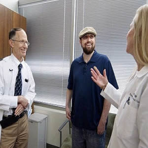 Richard Hotchkiss, MD, a professor of anesthesiology (left), and Jane Blood (right), a nurse manager in the Department of Anesthesiology's Division of Clinical and Translational Research, talk with Greg Porter, 34, of Nashville, Ill., who has recovered fr